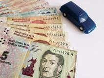 argentine banknotes and figure of a car in dark blue