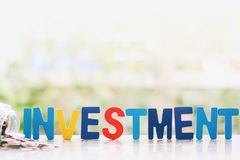 Investment wooden word with coins in the glass jar against blurred natural background stock images