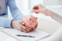 Investments and savings plan. Financial advisor holding a piggy bank and customer inserting a coin: investments, savings plan and retirement fund concept Stock Image