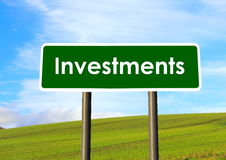 Investments Sign. A road sign saying investments on a scenic background royalty free stock photos