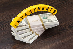 Investments, word made by letter, stack of dollar bills Royalty Free Stock Photography