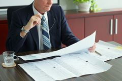 Investor with blueprint. Investor looking at the blueprint of the building stock photography