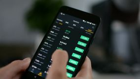 Investor checking Bitcoin, Ethereum and other altcoin cryptocurrency price index on mobile phone screen, cryptocurrency
