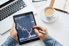 Investor, der die Änderung der Börse auf Tablette aufpasst lizenzfreies stockfoto