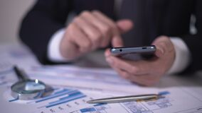 Investor scrolling market newswire on smartphone, examining data for new project