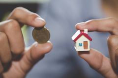 Investor show hand holding a model home and coin , Saving money for buy a new house and loan for plan business investment for real. Estate in the future concept royalty free stock photo