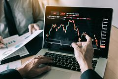 Investors are pointing to laptops that have investment information stock markets and partners taking notes and analyzing. Performance data stock images