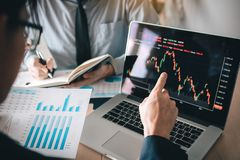 Investors are pointing to laptops that have investment information stock markets and partners taking notes and analyzing. Performance data royalty free stock images