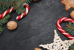 Invierno background Tablero negro con las decoraciones en la esquina ramas del abeto, palillos del caramelo, nuts y decorativo Imagen de archivo libre de regalías