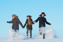 Invierno corriente feliz de la gente joven al aire libre Foto de archivo