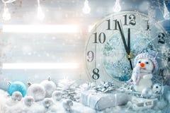 Invierno de la Navidad un fondo, el pequeño muñeco de nieve se coloca con un reloj Feliz Año Nuevo Feliz Navidad Fotografía de archivo libre de regalías