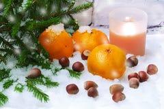 Invierno de la vela de la avellana de la nieve de las mandarinas Fotografía de archivo libre de regalías