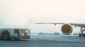 Invierno del aeropuerto El tractor de la remolque es avión de pasajeros cercano Cielo nublado metrajes