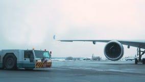Invierno del aeropuerto El tractor de la remolque es avión de pasajeros cercano Cielo nublado almacen de metraje de vídeo
