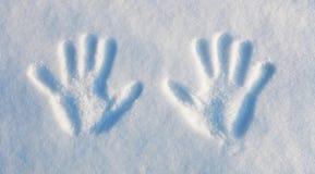 Invierno - dos handprints en la nieve. Imagen de archivo libre de regalías