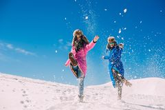 Invierno, dos muchachas que se divierten en la nieve en las montañas Fotografía de archivo