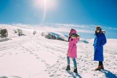 Invierno, dos muchachas que se divierten en la nieve en las montañas Imágenes de archivo libres de regalías