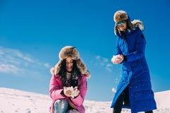 Invierno, dos muchachas que se divierten en la nieve en las montañas Foto de archivo libre de regalías