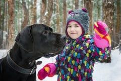 Invierno en el bosque una niña toma el pelo un perro grande con un panecillo Imágenes de archivo libres de regalías