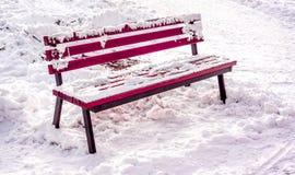 Invierno en el parque de la ciudad con la alfombra blanca cristalina fresca de la nieve y el banco marrón de madera con nieve en  Imagen de archivo