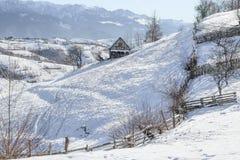Invierno en un pueblo de montaña rumano con los Cárpatos Imagen de archivo libre de regalías