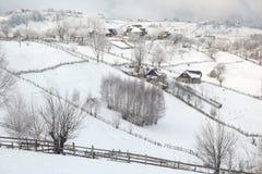 Invierno en un pueblo de montaña rumano con los Cárpatos Fotos de archivo