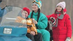 Invierno Familia en la ropa colorida que se sienta en las bebidas calientes de la moto de nieve, el hablar y de la consumición de metrajes