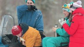 Invierno Familia en la ropa colorida que se sienta en la moto de nieve y las bebidas calientes de consumición de los termos Un ni almacen de video