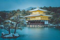Invierno hermoso estacional del pabellón de oro del templo de Kinkakuji con la nieve blanca que cae en Kyoto, Japón fotografía de archivo