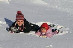Invierno: mama con el bebé en nieve Fotos de archivo