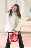 Invierno: Mujer asiática con el bolso de compras del día de fiesta Fotos de archivo libres de regalías