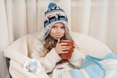Invierno, niña en casa en una butaca con la taza grande de té caliente, en sombrero hecho punto caliente debajo de la manta de la foto de archivo libre de regalías