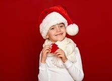 Invierno, niño, concepto de la Navidad - la muchacha feliz en lanas del árbol de abeto de la demostración del sombrero de santa j Foto de archivo libre de regalías