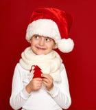 Invierno, niño, concepto de la Navidad - la muchacha feliz en lanas del árbol de abeto de la demostración del sombrero de santa j Fotos de archivo