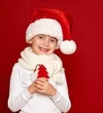 Invierno, niño, concepto de la Navidad - la muchacha feliz en lanas del árbol de abeto de la demostración del sombrero de santa j Fotografía de archivo