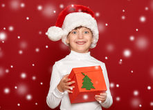 Invierno, niño, concepto de la Navidad - muchacha feliz en el sombrero de santa con Foto de archivo