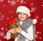 Invierno, niño, concepto de la Navidad - muchacha feliz en el sombrero de santa con Fotografía de archivo libre de regalías