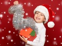 Invierno, niño, concepto de la Navidad - muchacha feliz en el sombrero de santa con Fotos de archivo libres de regalías