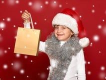 Invierno, niño, concepto de la Navidad - muchacha feliz en el sombrero de santa con Fotos de archivo