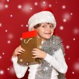 Invierno, niño, concepto de la Navidad - muchacha feliz en el sombrero de santa con Foto de archivo libre de regalías