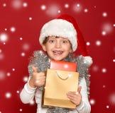 Invierno, niño, concepto de la Navidad - muchacha feliz en el sombrero de santa con Imagen de archivo libre de regalías