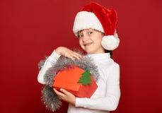 Invierno, niño, concepto de la Navidad - muchacha feliz en el sombrero de santa con el juguete del árbol de abeto de la demostrac Imágenes de archivo libres de regalías