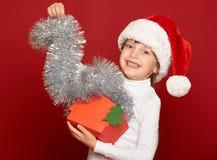 Invierno, niño, concepto de la Navidad - muchacha feliz en el sombrero de santa con el juguete del árbol de abeto de la demostrac Imagenes de archivo
