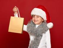 Invierno, niño, concepto de la Navidad - muchacha feliz en el sombrero de santa con el regalo de la caja en rojo Fotografía de archivo