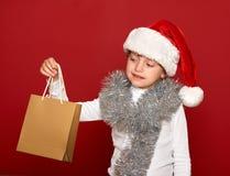 Invierno, niño, concepto de la Navidad - muchacha feliz en el sombrero de santa con el regalo de la caja en rojo Fotos de archivo