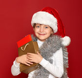 Invierno, niño, concepto de la Navidad - muchacha feliz en el sombrero de santa con el regalo de la caja en rojo Foto de archivo