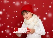 Invierno, niño, concepto de la Navidad - muchacha feliz en sombrero con la caja g Foto de archivo