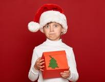 Invierno, niño, concepto de la Navidad - muchacha sorprendida en sombrero del ayudante de santa con el regalo de la caja en rojo Fotos de archivo