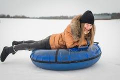 Invierno, ocio, deporte y gente un concepto - la muchacha feliz o la mujer que resbala en el tubo de la nieve Fotografía de archivo