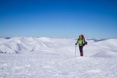 Invierno que camina en las montañas en las raquetas con una mochila y una tienda Imagenes de archivo